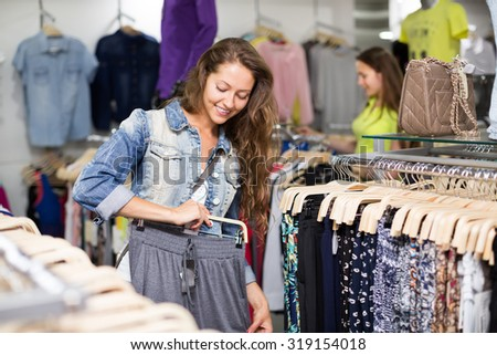 Young woman selecting pants in the shopping center