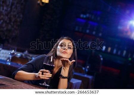 Young woman sending a romantic blow kiss in nightclub