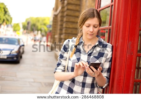 young woman sending a text in london - stock photo