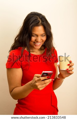 young woman sending text with coffee - stock photo