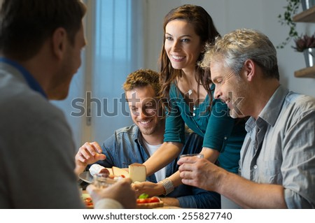 Young woman serving plate of cheese to man in kitchen