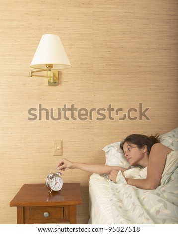 Young woman setting alarm clock - stock photo