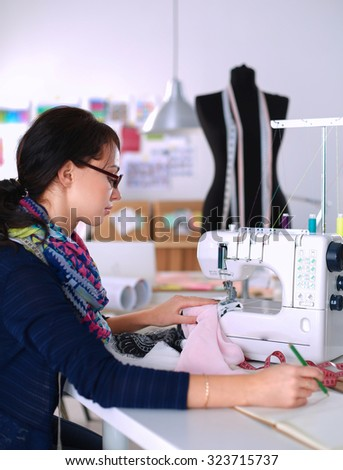 Young woman sewing while sitting at her working place