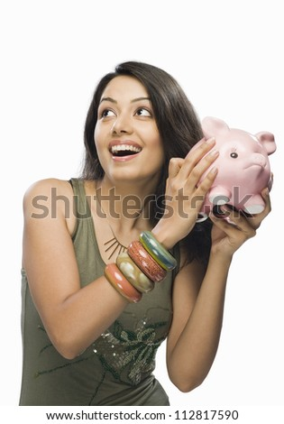 Young woman shaking a piggy bank - stock photo
