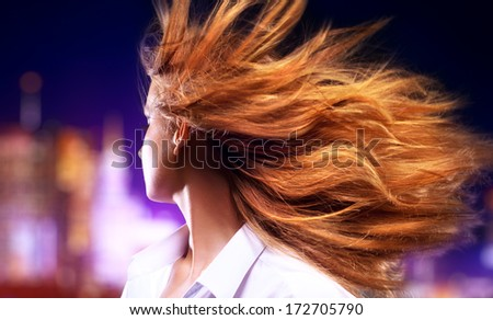 Young woman shaking hair. On night city background. - stock photo