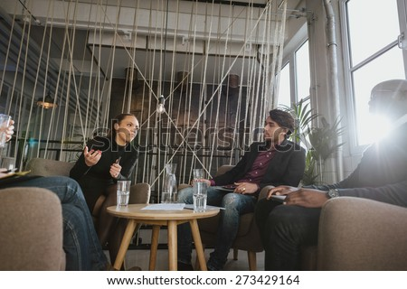 Young woman sharing her ideas during meeting in office. Creative young people discussing new project. - stock photo
