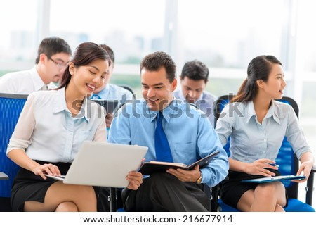 Young woman sharing some information on laptop with her colleague during the business seminar - stock photo