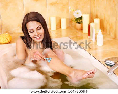Young woman shaving her legs in  bath. - stock photo