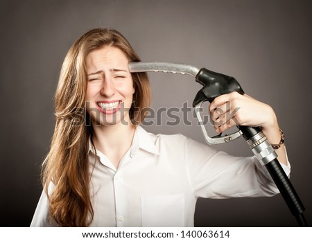 young woman shooting herself with a fuel pump nozzle - stock photo