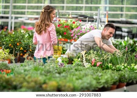 Young woman shop flowers in greenhouse