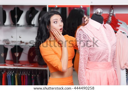 Young woman shopper astonished price on the dress. Young woman shopping in a clothing store. Caucasian shopper girl choosing pink dress in shop during sale. Woman shopping for dress. Fashion shopping - stock photo