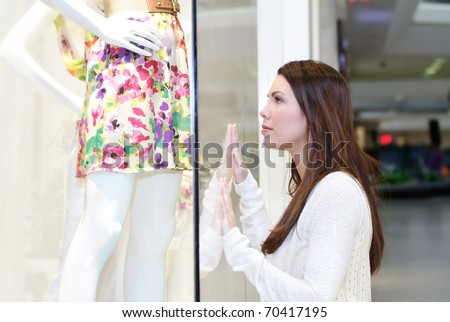Young woman shopping at the mall for a dress or skirt, looking at a store window