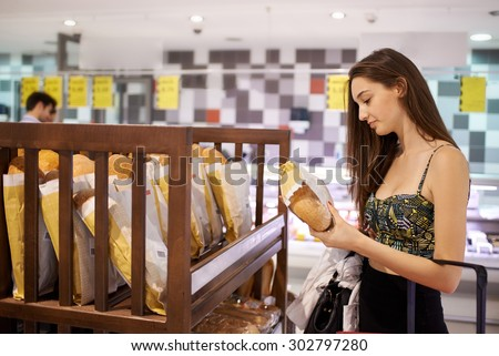 young woman shopping for fruits and vegetables in produce department of a grocery store supermarket - stock photo