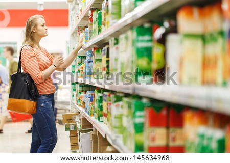 Young woman shopping for juice in produce department of a supermarket
