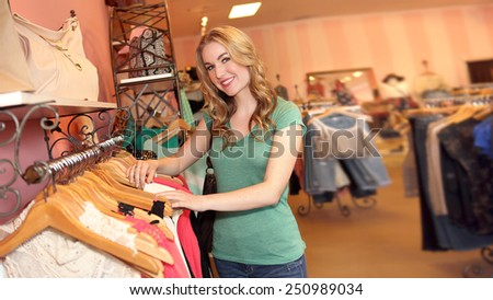 Young woman shopping in clothing store - stock photo
