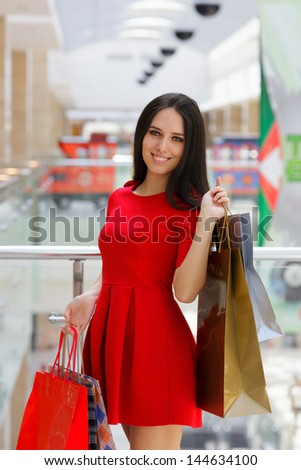 Young Woman Shopping in Mall - Red dress, shopping and gift bags - stock photo