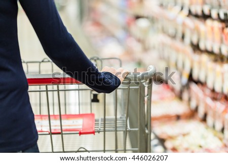 Young woman shopping in the lunch meat section at the grocery store.