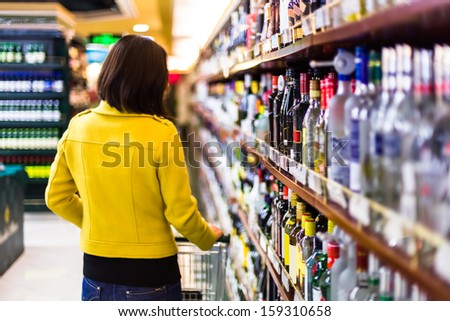 Young woman shopping in the supermarket,wine shelves - stock photo