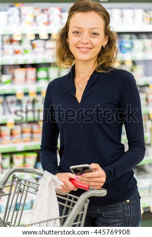 Young woman shopping in the yogurt section at the grocery store.