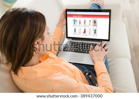 Young Woman Shopping On Laptop In Her Room - stock photo