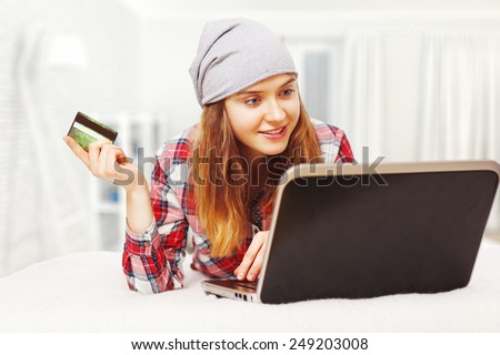 Young woman shopping online with a credit card - stock photo