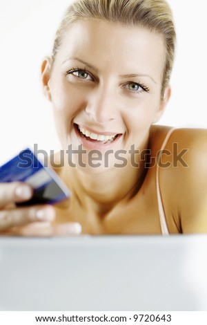 young woman shopping through her laptop with credit card - stock photo