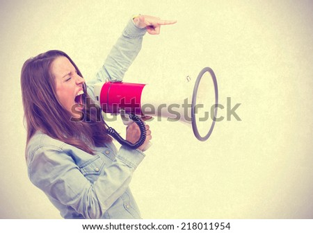 young woman shouting by megaphone - stock photo