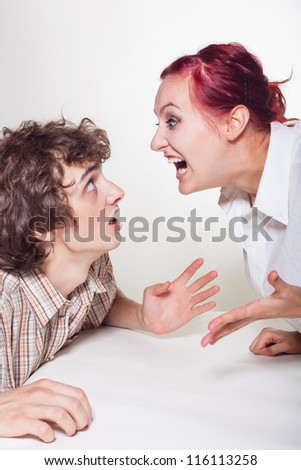Young woman shouting menacingly at her husband on a light background - stock photo