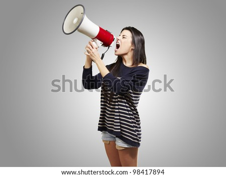 young woman shouting with a megaphone against a grey background - stock photo
