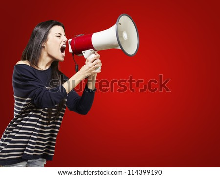 young woman shouting with a megaphone against a red background - stock photo