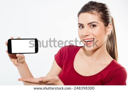 Young woman show display of mobile cell phone with white screen and smiling on a white background - stock photo