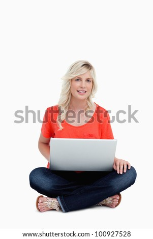 Young woman showing a great smile and using her laptop while sitting cross-legged
