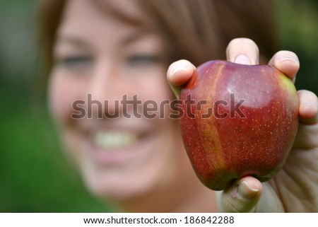 Young woman showing an apple
