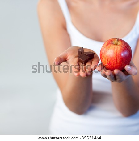 Young woman showing chocolate and apple at the camera focus on chocolate - stock photo