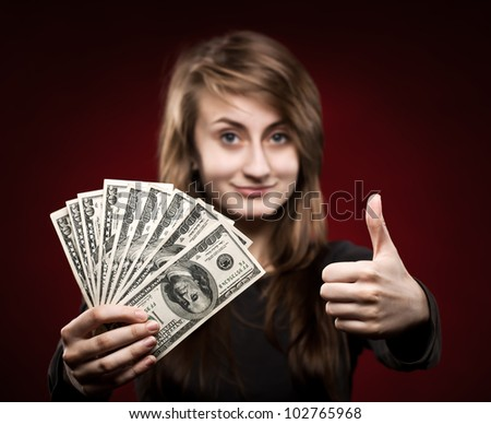 Young woman showing fan of money and sign OK with fingers - stock photo