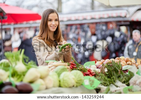 Young woman showing farmer which peppers she'd like to buy. At the market. - stock photo