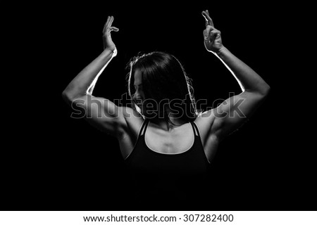 Young woman showing her muscles - in black and white - stock photo