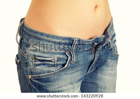 young woman showing her perfect waist and open jeans isolated on white background