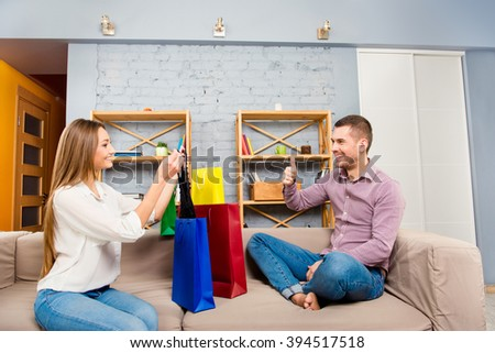 Young woman showing her purchaces in color bags to her man