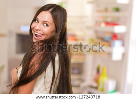 Young Woman Showing Her Tongue in front of her fridge - stock photo