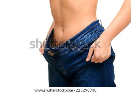 young woman showing how much weight she lost on white background,isolated. - stock photo