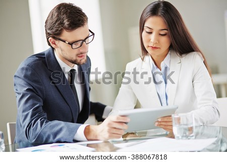 Young woman showing information on touchpad to her colleagues