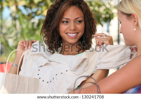 Young woman showing off a new top to a girlfriend - stock photo