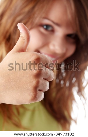 Young woman showing OK. Looking at camera and smiling.  White background.