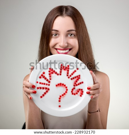 Young woman showing plate with vitamins pills set out the word vitamins in studio on white background - stock photo