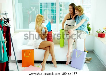 Young woman showing purchases to her girlfriends - stock photo