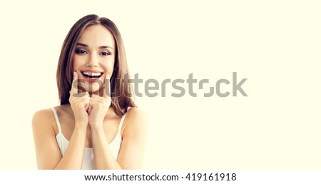 young woman showing smile, in casual smart clothing, with copyspace for slogan or text message - stock photo