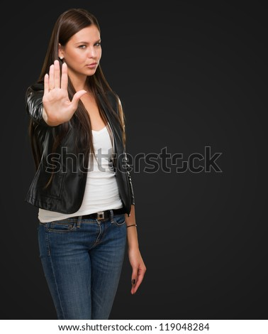 Young Woman Showing Stop Hand Gesture against a black background - stock photo