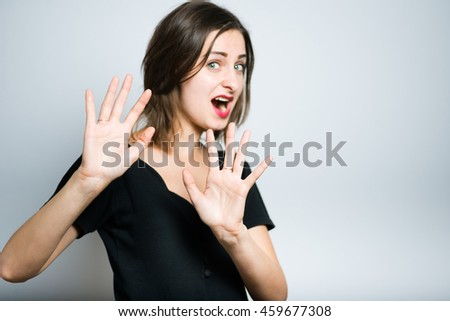 young woman showing stop sign, studio photo isolated on a gray background - stock photo