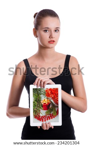 Young woman showing tablet computer touch pad gadget with the gift box on a screen. Christmas concept. - stock photo